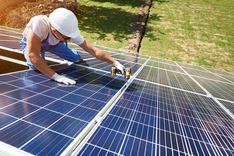 Arbeiter sitzt auf einer Solaranlage